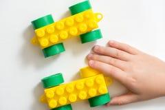 Spielzeugfarbdesigner, Zug die Kinderspiele und die Gestalten aus Würfeln heraus Hände des Kindes Auf einem weißen Hintergrund lizenzfreies stockfoto