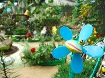 Spielzeugfrosch auf dem Hintergrund eines blühenden Sommergartens stockfotografie