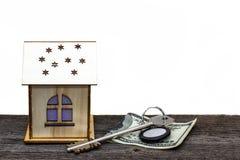 Spielzeughaus mit Schlüsseln und Bargeld auf altem hölzernem Brett, auf weißem lokalisiertem Hintergrund lizenzfreie stockbilder