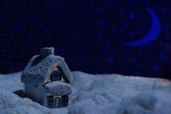 Spielzeughaus steht im Schnee während der Nacht der Wolle Stockfotos