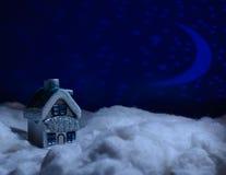 Spielzeughaus steht im Schnee während der Nacht der Wolle Stockfoto