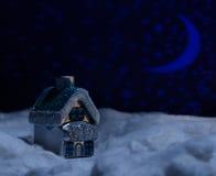Spielzeughaus steht im Schnee während der Nacht der Wolle Lizenzfreies Stockbild