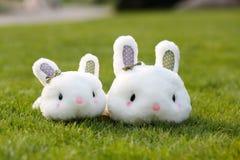 Spielzeugkaninchen mit zwei Plüschen im Gras lizenzfreie stockfotografie