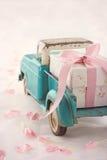 Spielzeuglastwagen, der eine Geschenkbox mit rosa Band transportiert Lizenzfreies Stockbild