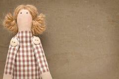 Spielzeugmädchen auf altem braunem Hintergrund Lizenzfreie Stockbilder