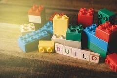 Spielzeugplastikziegelstein mit Alphabet deckt Wort GESTALT auf Holztisch mit Ziegeln Lizenzfreies Stockfoto