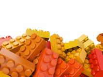 Spielzeugplastikziegelsteinhintergrund in den warmen Farben Stockbilder