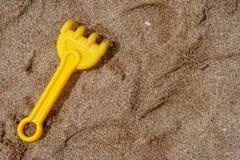 Spielzeugrührstangen der Kinder und Spuren von ihnen im Sand stockfotografie