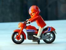 Spielzeugradfahrer auf rotem Fahrrad Lizenzfreie Stockfotografie