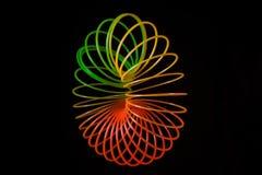 Spielzeugregenbogenspirale eingewickelt in einem Ring auf einem schwarzen Hintergrund Lizenzfreies Stockfoto