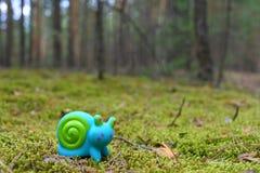 Spielzeugschnecke auf dem Moos lizenzfreie stockfotos
