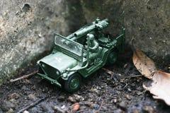 Spielzeugsoldatlaufwerk sein Jeep auf einem tränkenbodenboden Lizenzfreie Stockfotografie