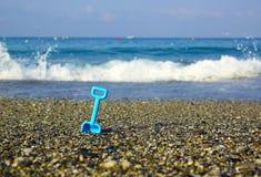 Spielzeugspaten auf dem Strand Stockfotografie