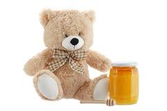Spielzeugteddybär lokalisiert auf Weiß mit Honig Lizenzfreie Stockfotos