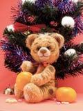 Spielzeugtiger mit Orangen unter einem Pelzbaum Lizenzfreie Stockfotos