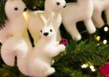 Spielzeugweihnachtsweißes flaumiges Eichhörnchen mit roter Kegel- und Rotwildnahaufnahme sitzt auf einem grünen Fichtenzweig und  Lizenzfreies Stockfoto