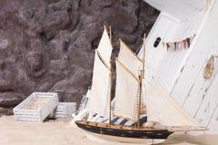 Spielzeugyacht und ruiniertes hölzernes Schiff Lizenzfreies Stockbild