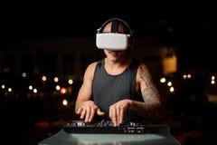 Spier en getatoeeerde nachtclub DJ in de glazen van de nachtvisie stock foto's