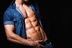 Spier en sexy jonge mens in jeansoverhemd met Stock Fotografie