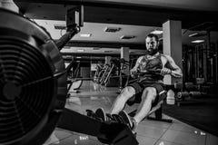 Spier geschikte mens die het roeien machine met behulp van bij gymnastiek stock foto's