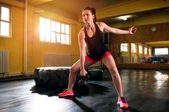 Spier geschikte vrouw die training met kettlebell in gymnastiek doen stock foto