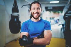Spier glimlachende bokser in handschoenen die zich met die wapens bevinden dichtbij ponsenzak worden gekruist in geschiktheidsgym royalty-vrije stock fotografie