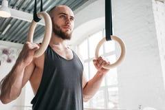Spier gymnastiek- ringen houden bij lichte gymnastiek en mens die weg kijken royalty-vrije stock afbeelding