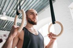 Spier gymnastiek- ringen houden bij lichte gymnastiek en mens die weg kijken royalty-vrije stock fotografie