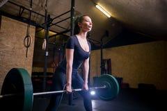 Spier jonge geschiktheidsvrouw die zware deadliftoefening in gymnastiek doen Stock Foto's