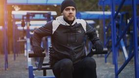 Spier jonge mens die oefening in openluchtgymnastiek in de winterpark doen stock foto