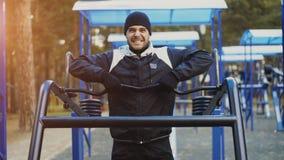 Spier jonge mens die oefening in openluchtgymnastiek in de winterpark doen stock foto's