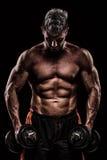 Spier jonge mens het opheffen gewichten op donkere achtergrond stock afbeeldingen