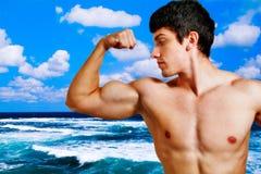 Spier mens die zijn bicepsen op het strand toont stock afbeelding