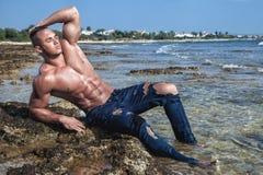 Spier natte naakte sexy kerel die op het strand met een naakt torso liggen stock fotografie