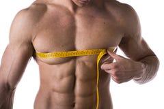 Spier shirtless jonge mens die borst en Pecs met meetlint meten stock afbeeldingen