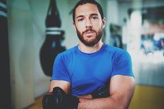 Spier sterke bokser in handschoenen die zich met die wapens bevinden dichtbij ponsenzak worden gekruist in geschiktheidsgymnastie Royalty-vrije Stock Foto