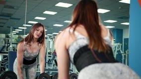 Spieratletenvrouw die in de gymnastiek het opheffen gewichten uitwerken Geschiktheidsmeisje die in de gymnastiek met domoren uito stock video