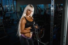 Spierblondevrouw die trekkracht UPS opleidingswapens met de riemen van de trxgeschiktheid in de de training gezonde levensstijl v stock afbeeldingen