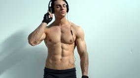 Spierbodybuilder die aan muziek met hoofdtelefoons luisteren stock videobeelden