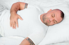 Spierbodybuilder met stammentatoegeringen die in bed slapen Stock Foto