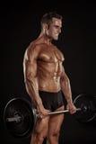 Spierbodybuilderkerel die oefeningen met grote domoor doen dumbb Stock Foto