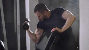 Spierbodybuilderkerel die oefeningen op bicepsen met domoor doen stock footage