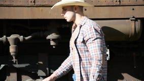 Spiercowboy, open overhemd op naakt torso, die door oude trein lopen stock video