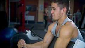 Spieren van één de jonge mens van de Sportenbodybuilder de harde opleidingsbiceps in gymnastiek stock footage