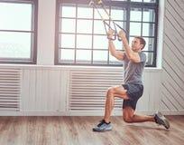 Spiergeschiktheid mannelijke het doen oefening met TRX Functionele training thuis met TRX-lijnen stock foto