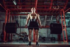 Spiergeschiktheidsmens die deadlift een barbell in modern geschiktheidscentrum doen Functionele opleiding Stock Foto's
