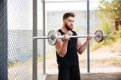 Spiergeschiktheidsmens die zware oefening doen die barbell in openlucht gebruiken stock afbeeldingen