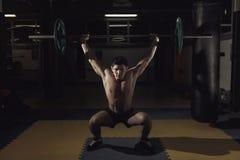 Spiermens bij een crossfitgymnastiek die een barbell opheffen Stock Foto