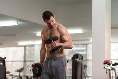 Spiermens die Bicepsen met Domoor uitoefenen Stock Foto