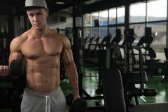 Spiermens die Bicepsen met Domoor uitoefenen Stock Afbeelding